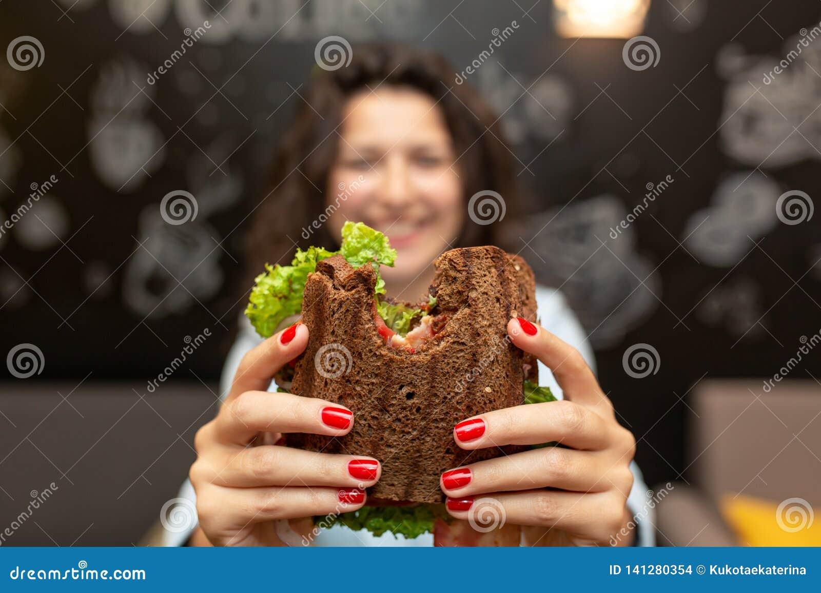 Protrait borrado engraçado do close up do sanduíche mordido posse da jovem mulher por suas duas mãos Sanduíche no foco Fundo escu