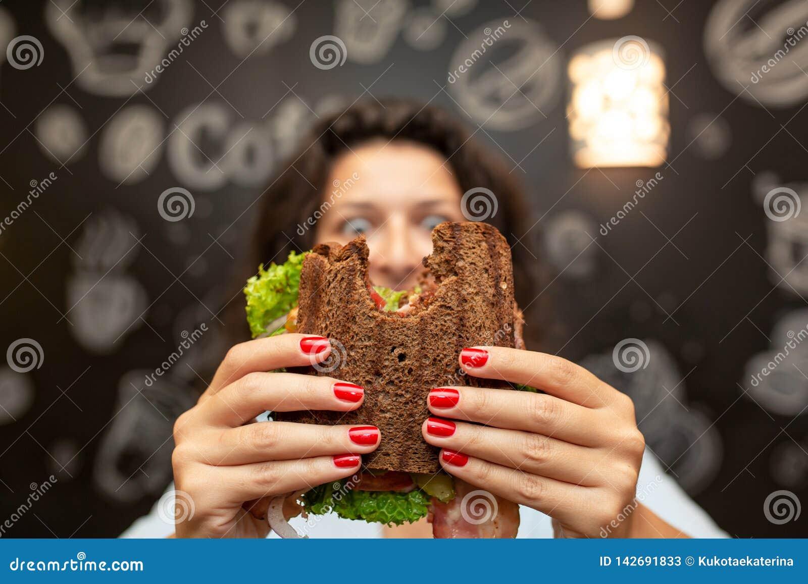 Protrait vago divertente del primo piano del panino pungente tenuta della giovane donna dalle sue due mani Panino a fuoco Fondo s