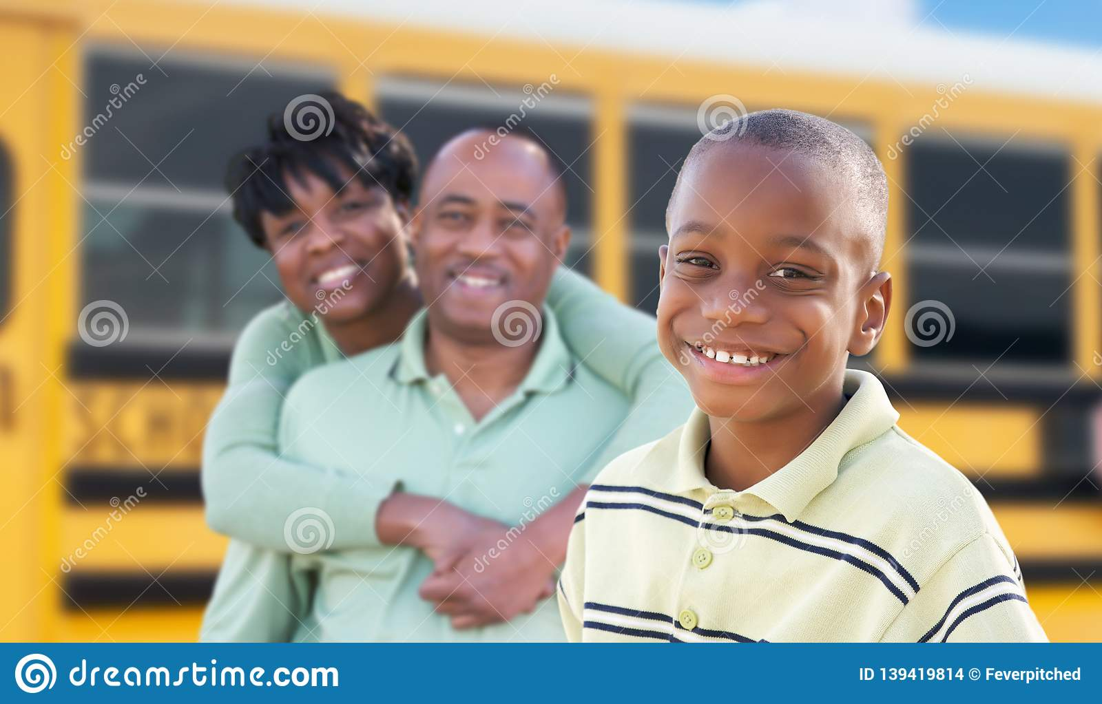 Proud African American Parents and Young Boy Near School Bus