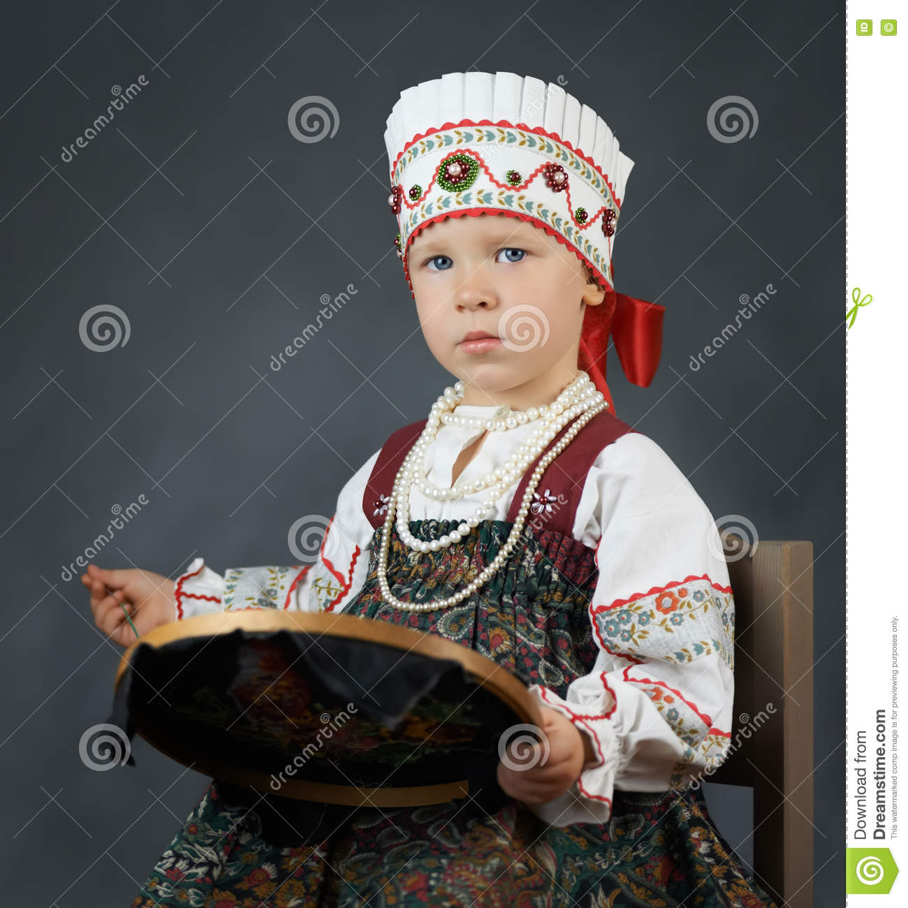 Proud little girl in the traditional russian sarafan during embroidering