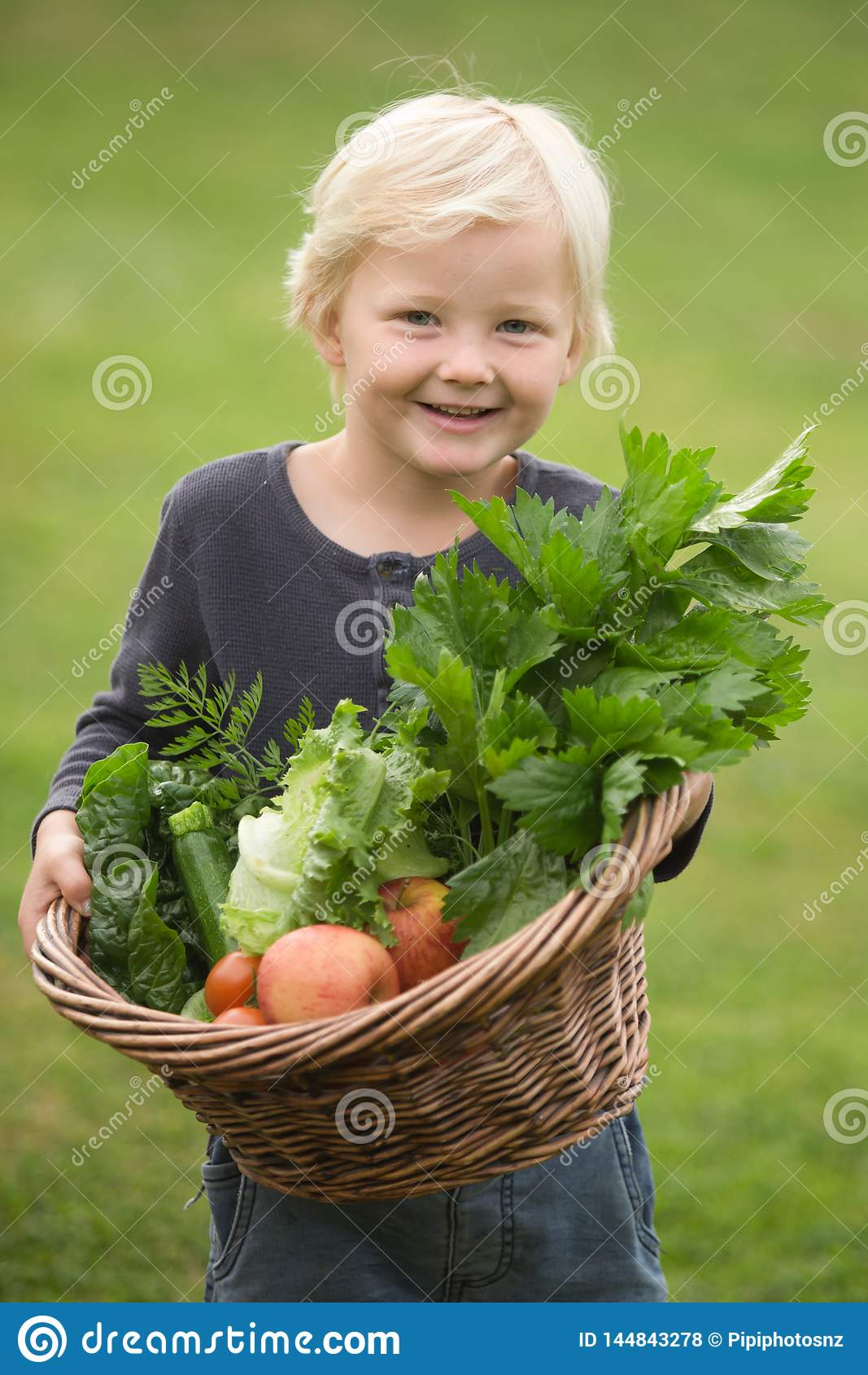 Young  blonde gardener proudly shows off his harvest