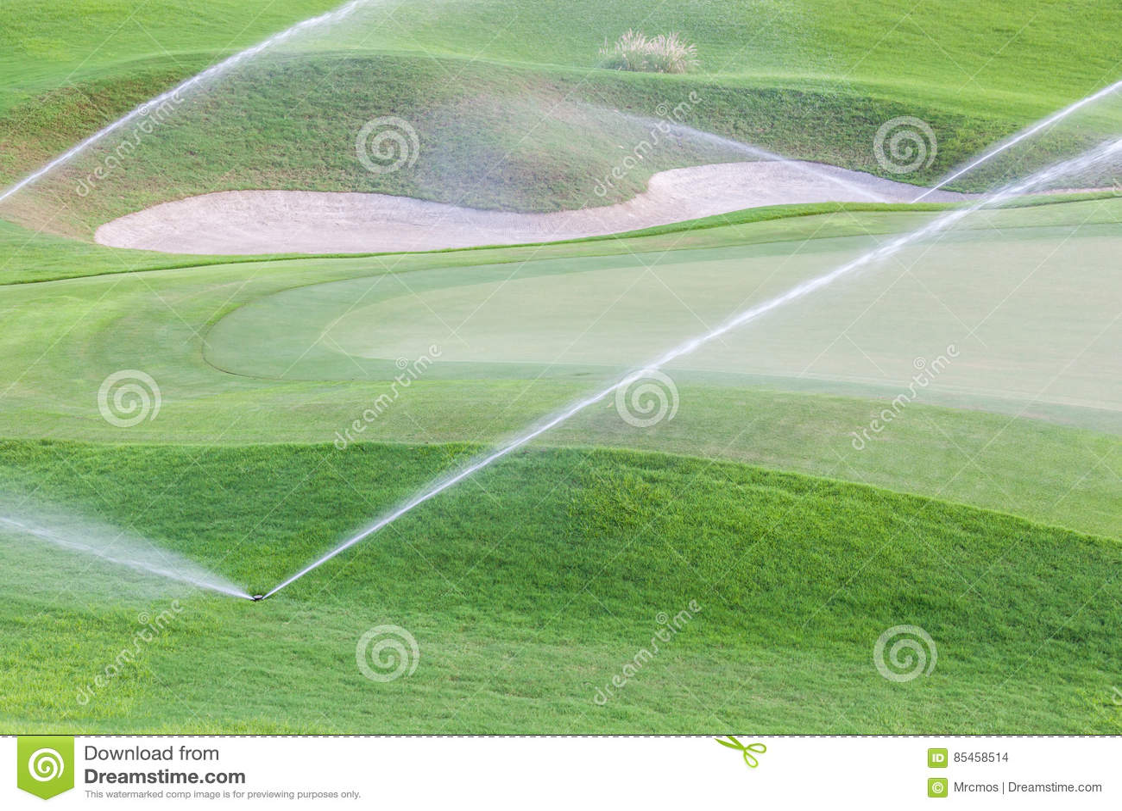 Provê o sistema molhando que trabalha no campo de golfe verde
