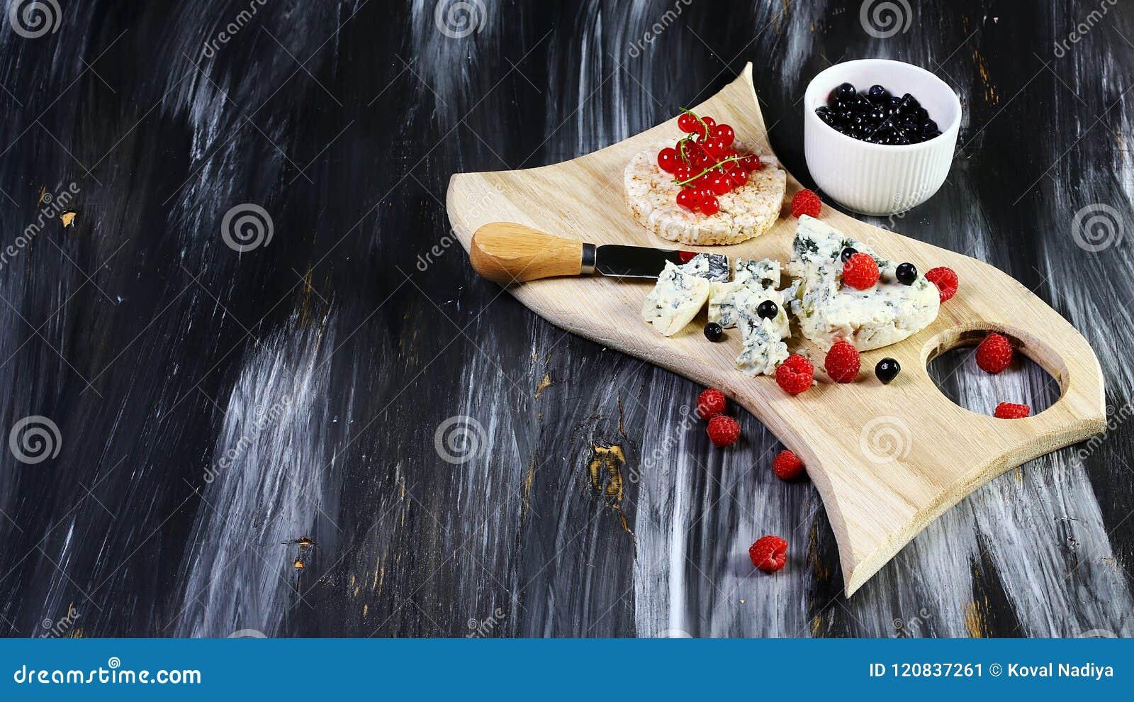 Provando o queijo do molde com frutos e as framboesas frescas das bagas, mirtilos no fundo de pedra do preto escuro