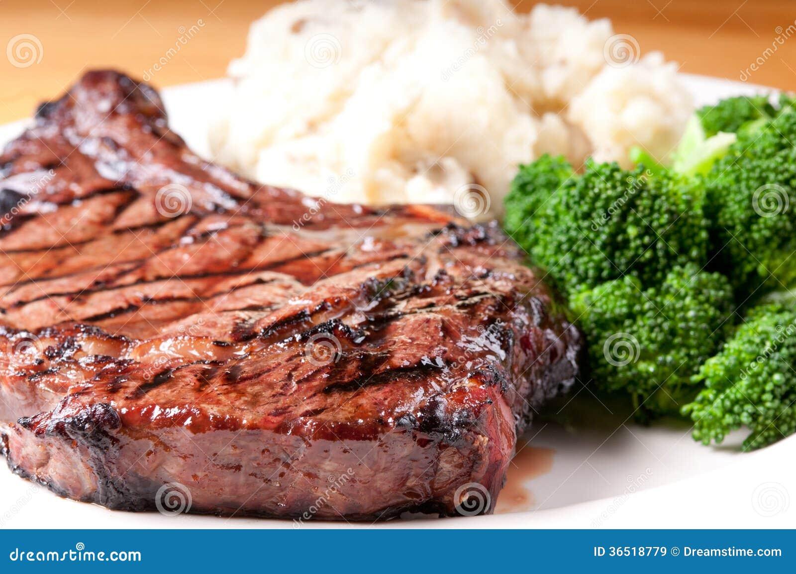 Provea de costillas el filete con los potatooes y brocolli triturados ajo