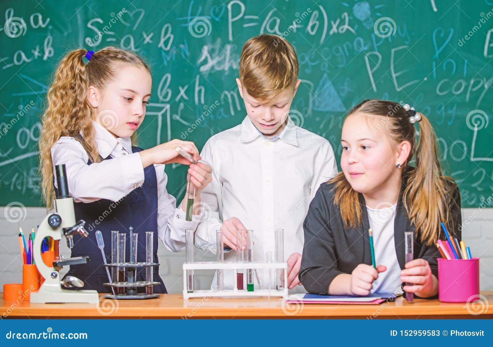 Provette con le sostanze educazione scolastica Ragazze ed esperimento della scuola di comportamento dello studente del ragazzo co