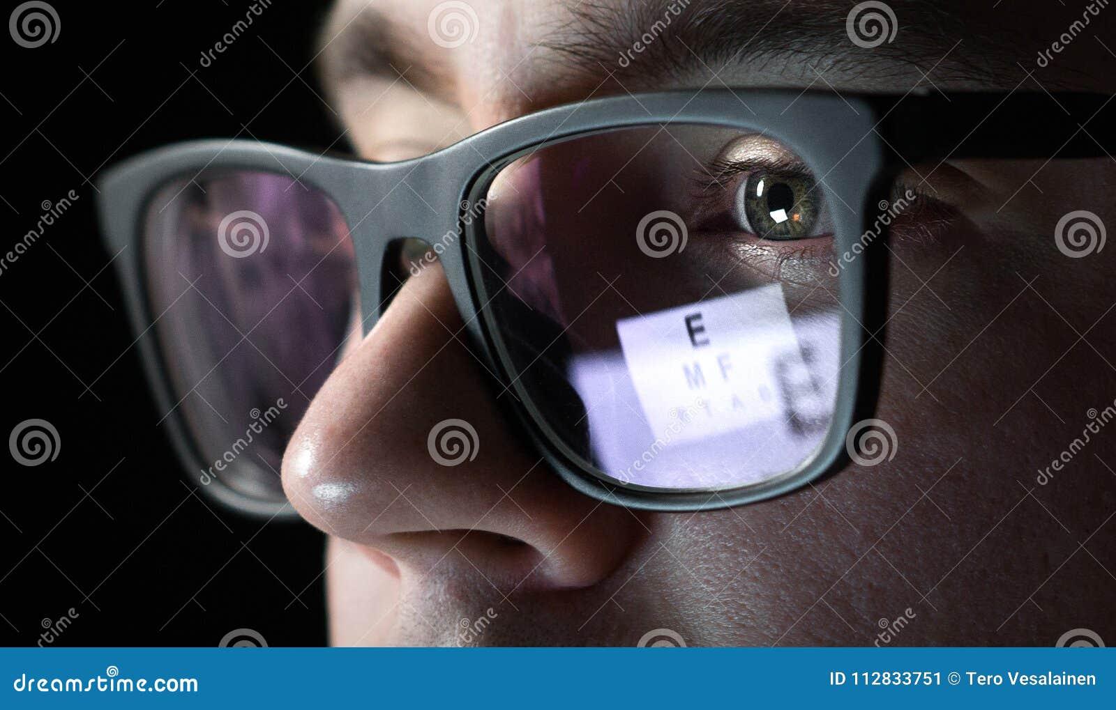 Prueba del ojo y concepto del examen Ciérrese para arriba de hombre con los vidrios