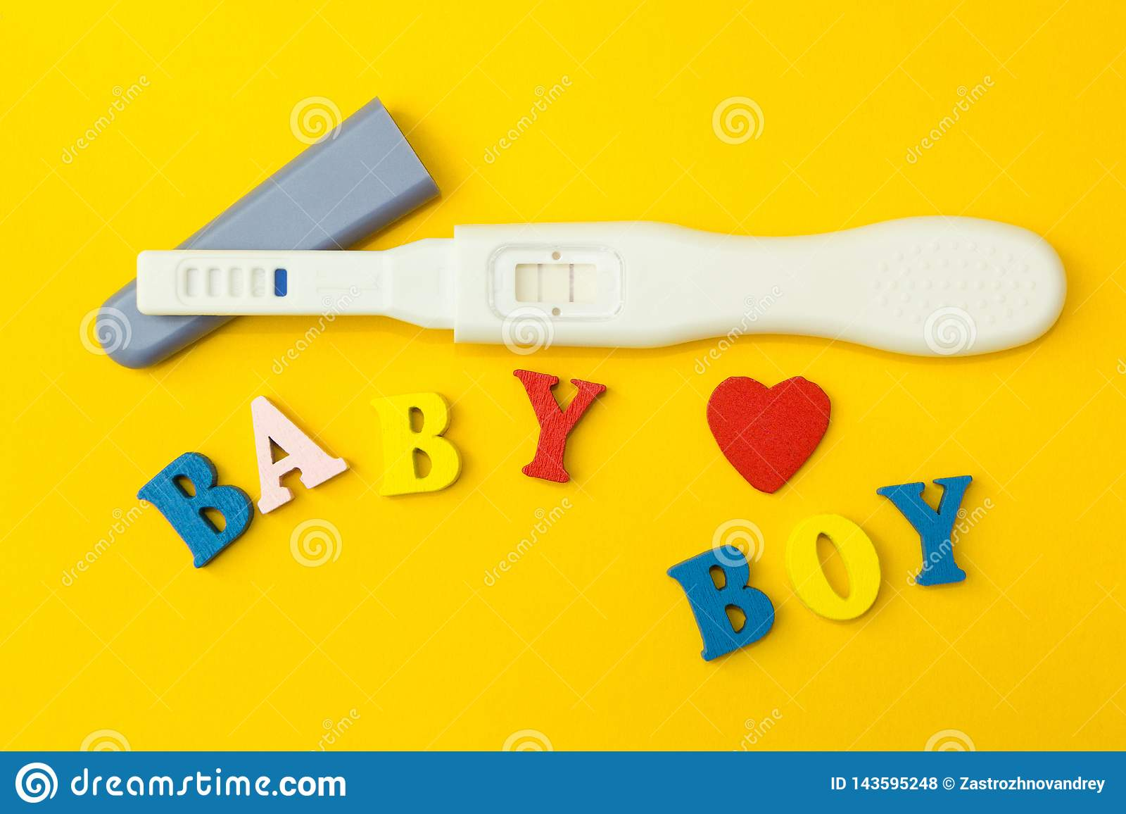 Prueba positiva para el embarazo, el corazón y la palabra 'bebé y muchacho 'en un fondo amarillo