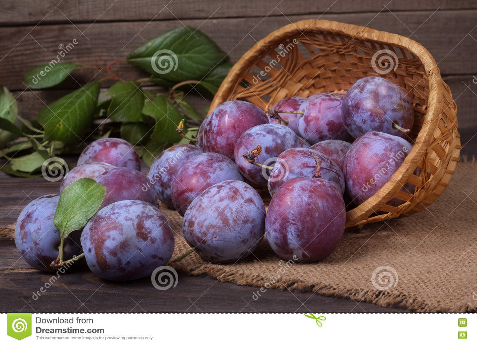Prune dans un panier en osier sur le fond en bois avec la toile à sac