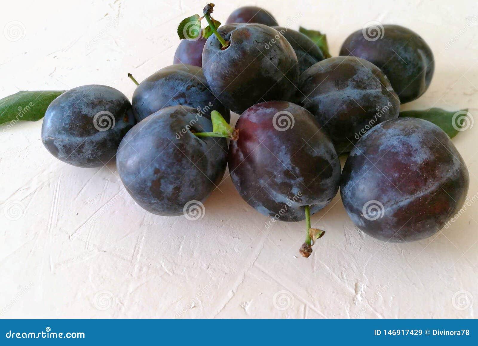Prune fraîche mûre sur une table concrète blanche