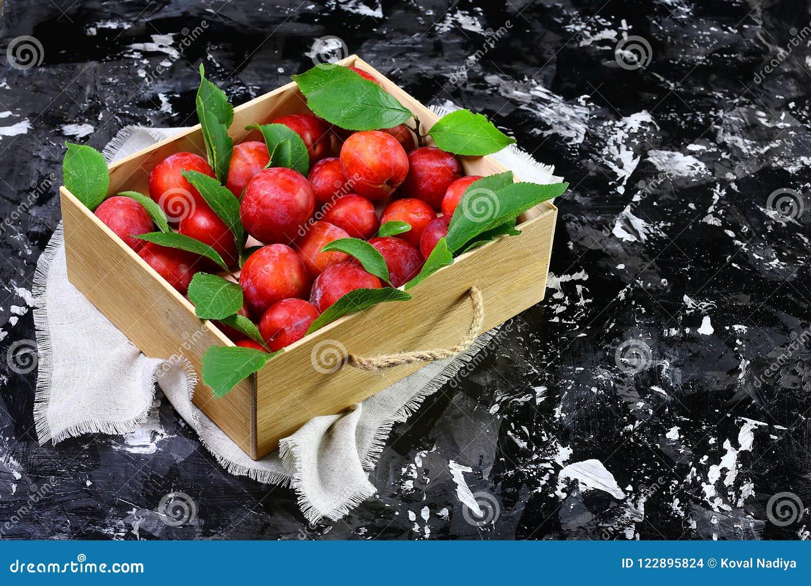 Prunes avec des feuilles dans une boîte en bois Sur un fond noir Vue supérieure Concept minimal de configuration de chute plate d