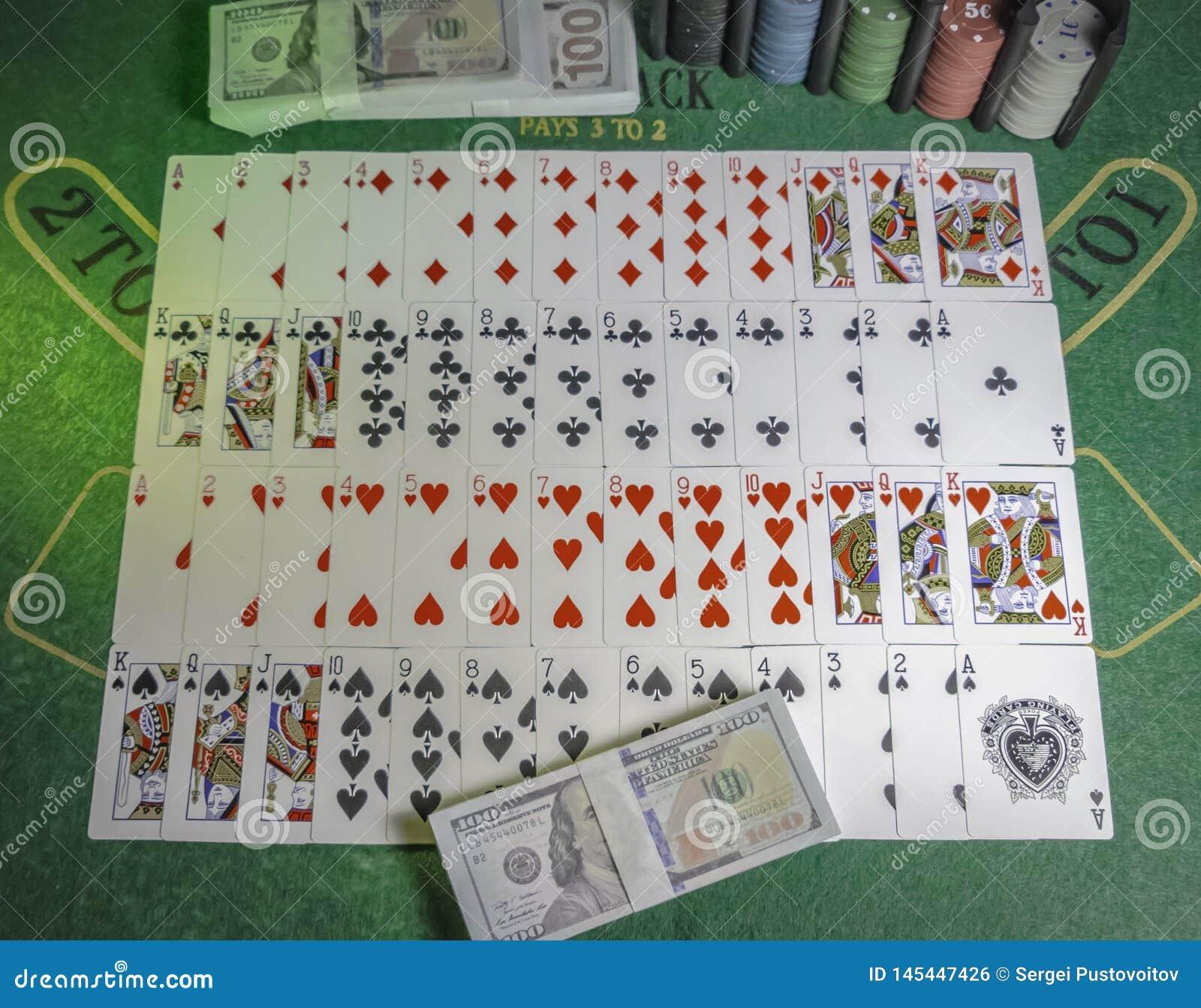 Pryda av spela kort, kasinochiper och packe av 100s av US dollar på den gröna tabellen för blackjacken som tänds med partilju