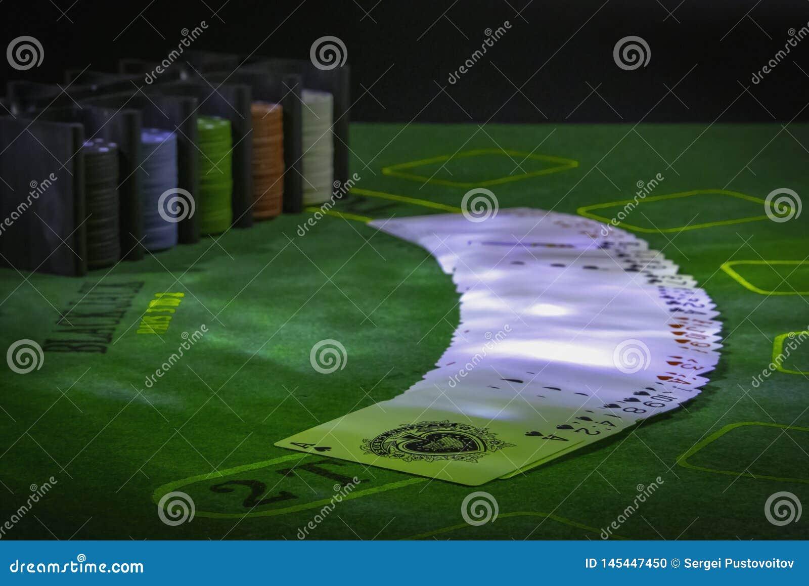 Pryda av spela kort och kasinochiper på den gröna tabellen för blackjacken som tänds med partiljus