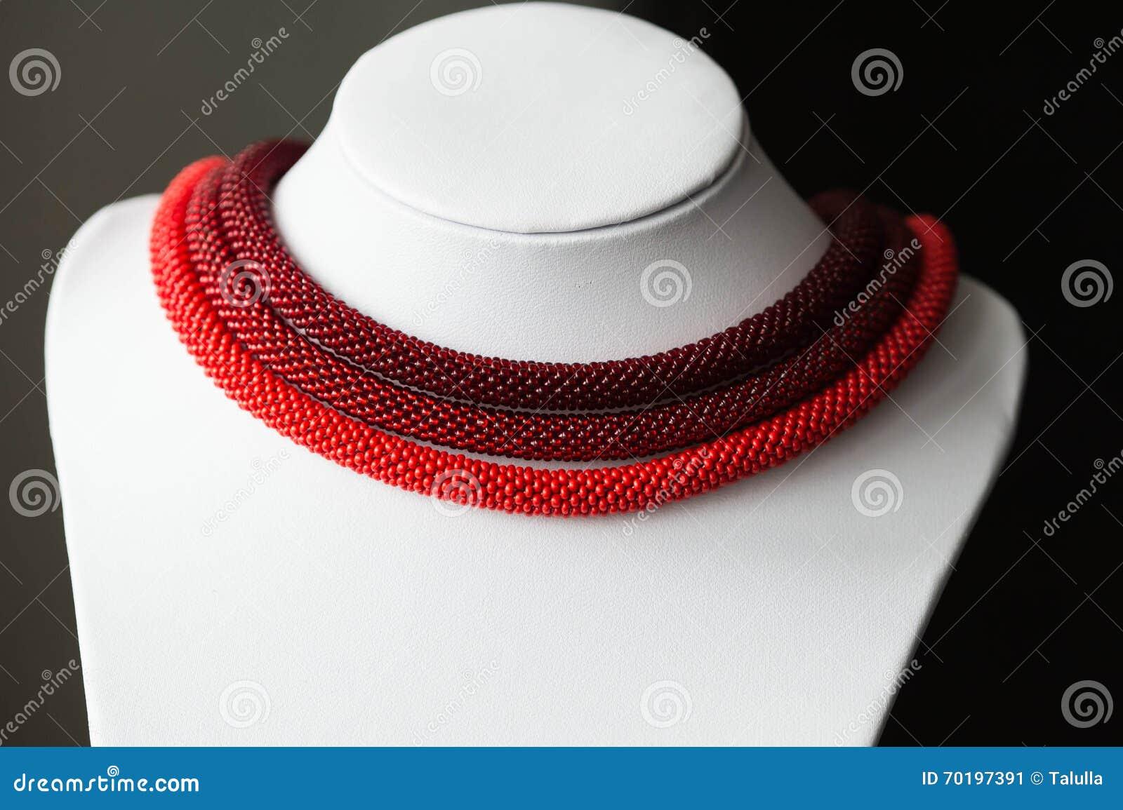 Prydd med pärlor halsband av röd färg från tre rep