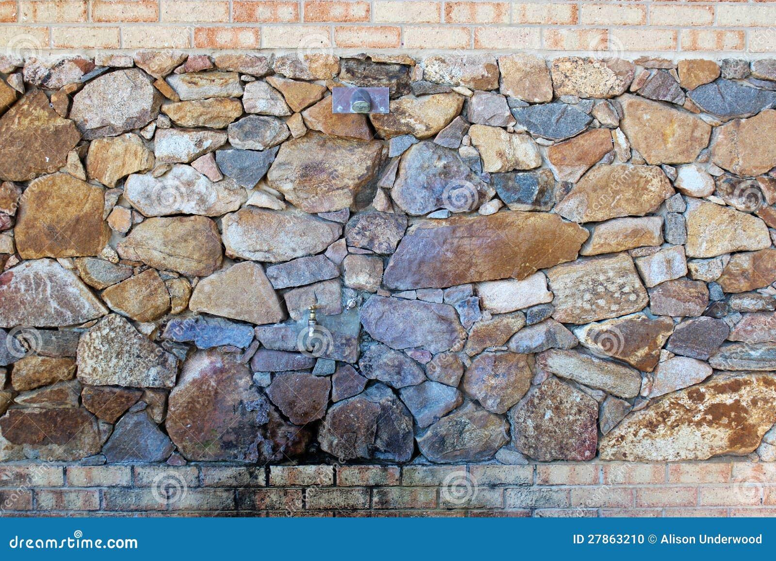 Prysznic i klepnięcie ustawiający w kamiennej ścianie