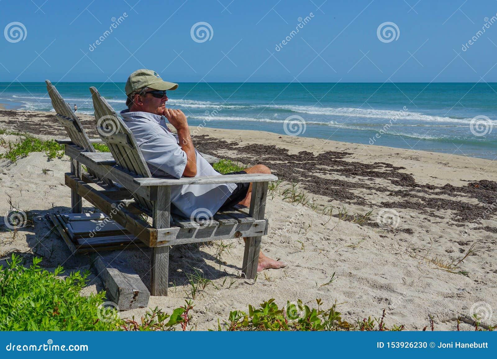 Przechodzić na emeryturę mężczyzny obsiadanie na krześle przegapia turkusowego błękita ocean