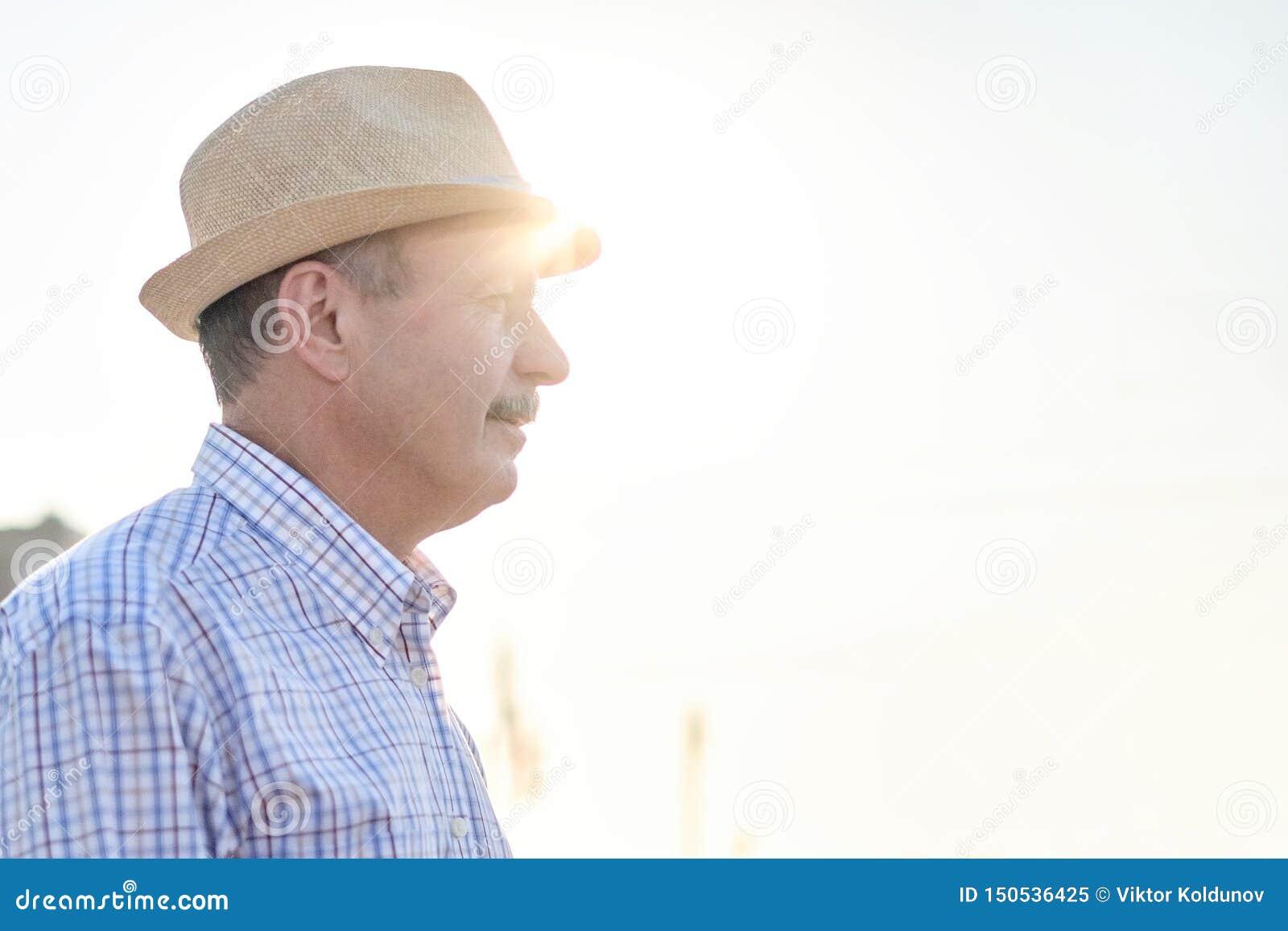 Przechodzić na emeryturę starszy latynoski mężczyzna z kapeluszową pozycją i ono uśmiecha się