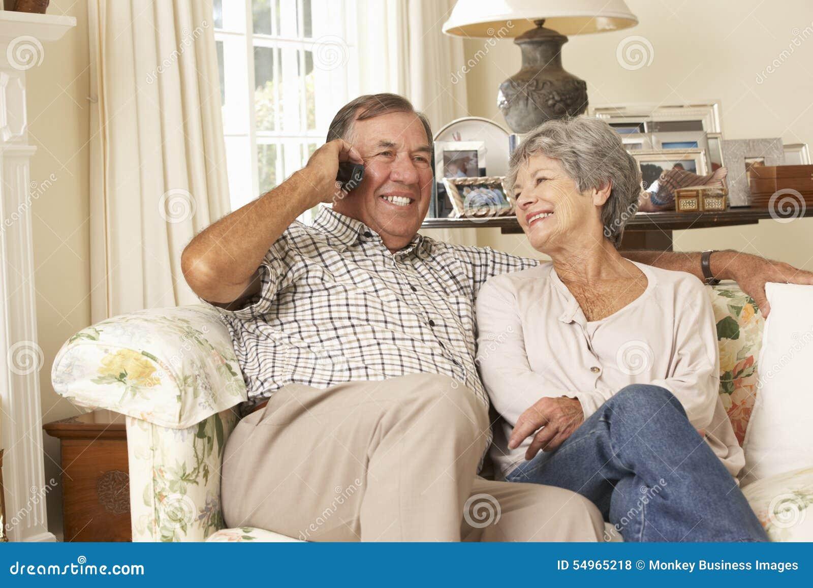 Przechodzić na emeryturę Starszy pary obsiadanie Na kanapie Opowiada Na telefonie W Domu Wpólnie