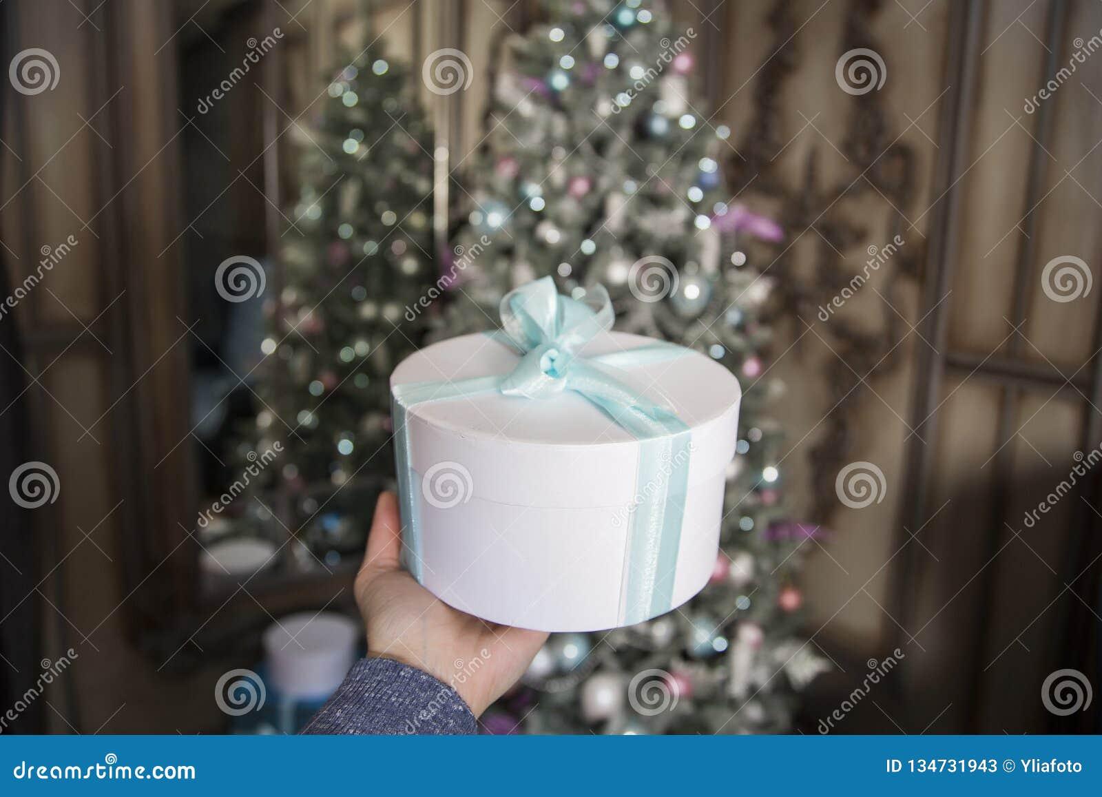 Przeciw tłu nowy rok dekorująca jedlina żeńska ręka trzyma białego prezent z zieloną taśmą