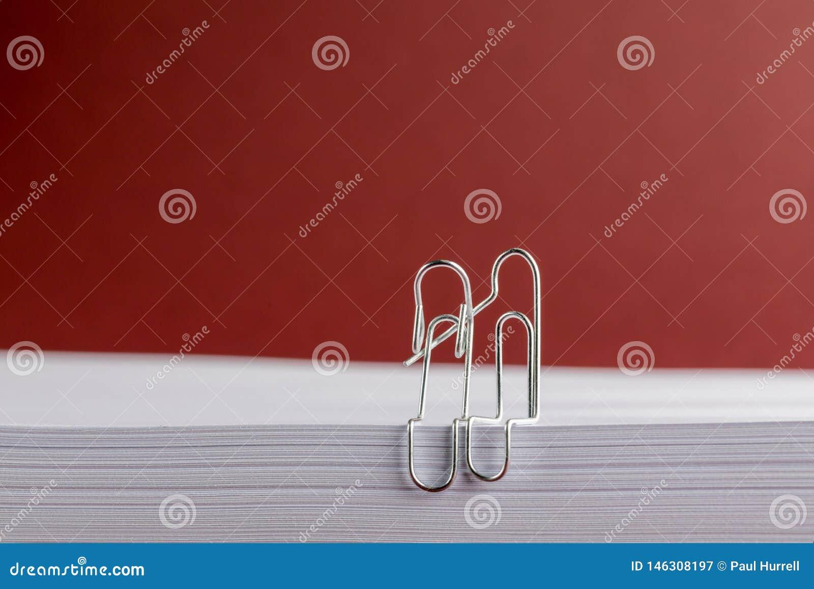 Przegięte papierowe klamerki Cuddling na białej księdze na Czerwonym tle