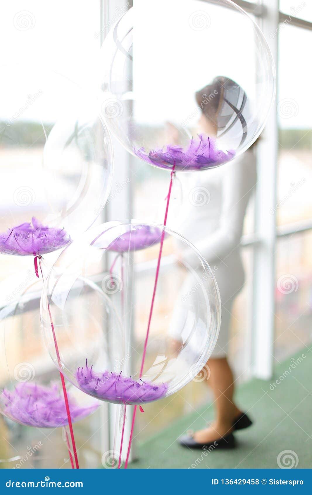 Przejrzyści helowi fiołków balony, kobieta w ciąży w rozmytym tle i