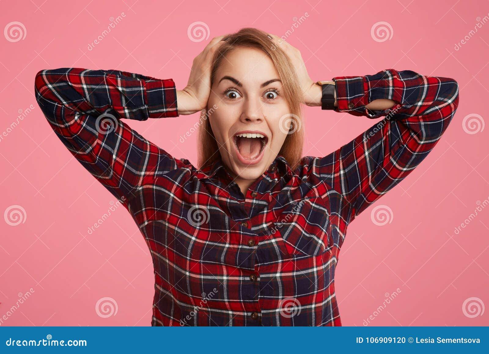 Przelękła szokująca młoda kobieta otwiera usta szeroko i krzyczy w terrorze, doesn ` t przewiduje widzieć jej fobię, utrzymanie r