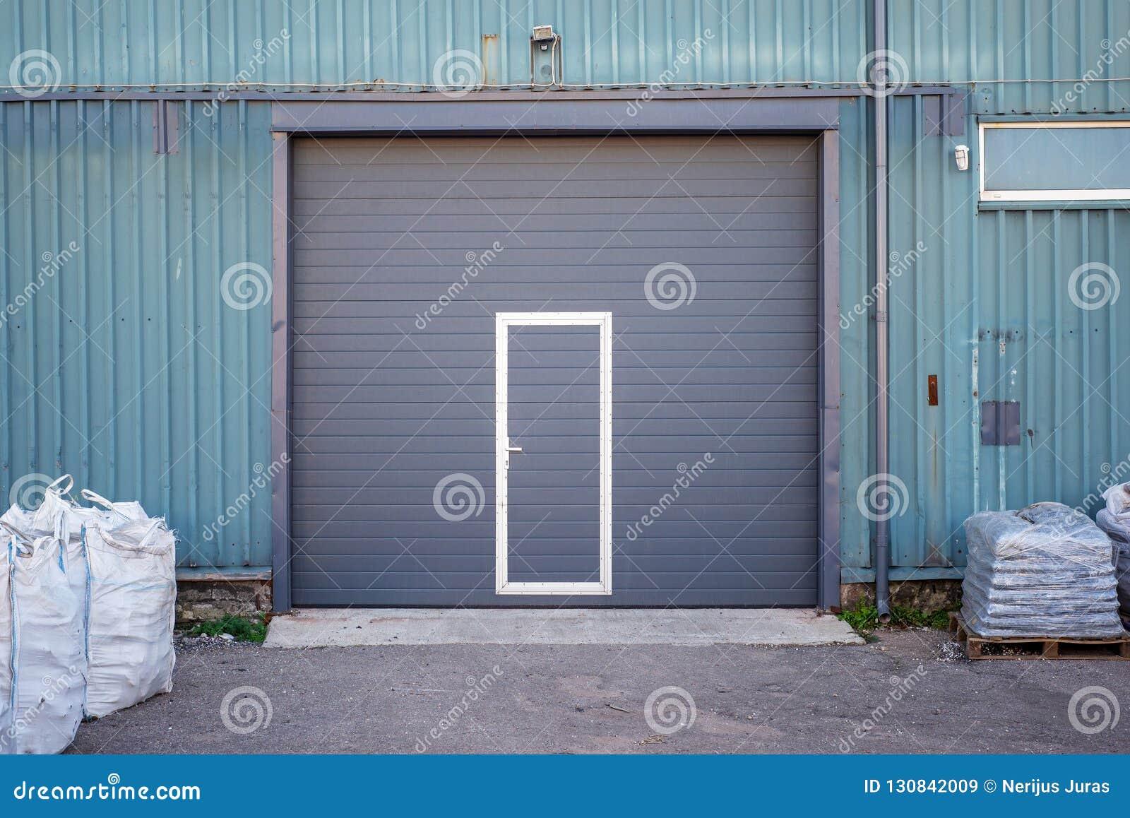 Przemysłowy magazyn z zmroku popielatym drzwi dla pojazdu