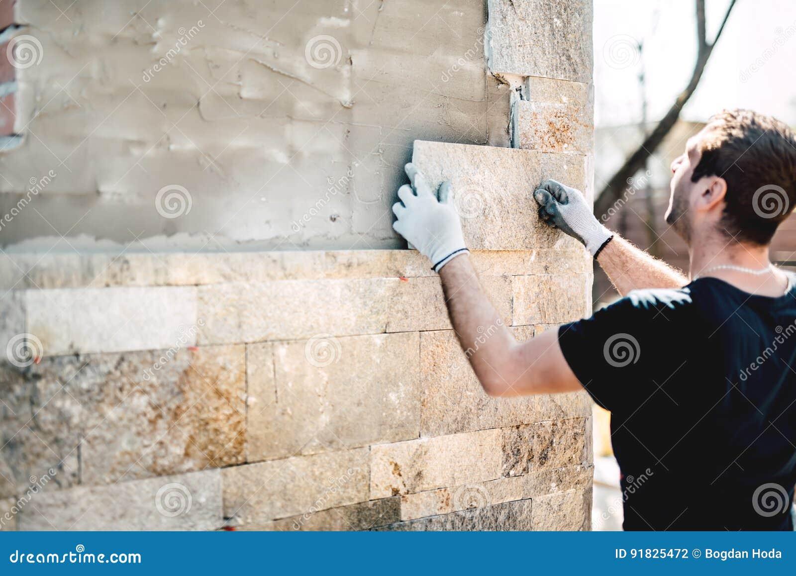 Przemysłu pracownik instaluje kamień płytki na architektonicznej domowej fasadzie