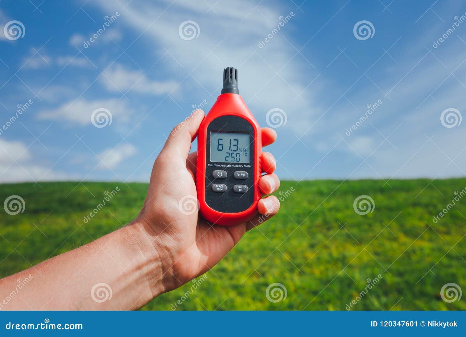 Przenośny termometr w ręce mierzy plenerową lotniczą temperaturę i wilgotność