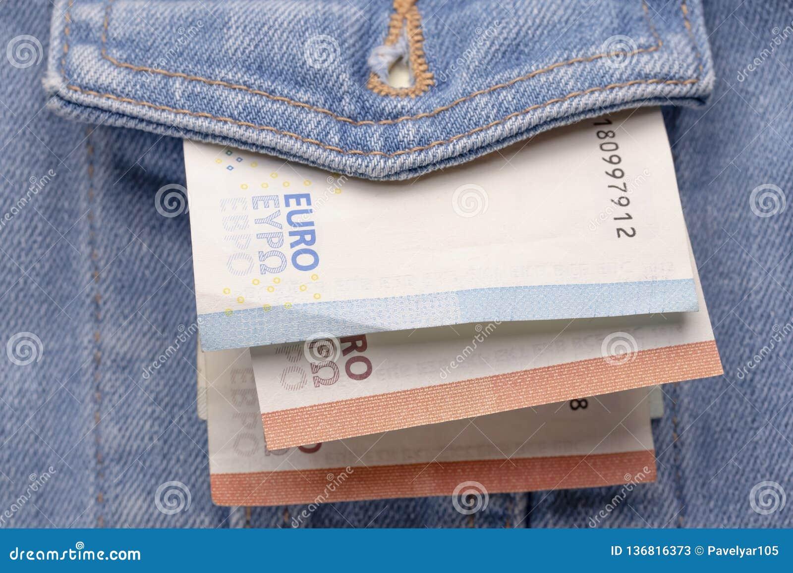 Przetarta klasyczna drelichowa kurtka w przodzie z małą ilością euro banknoty
