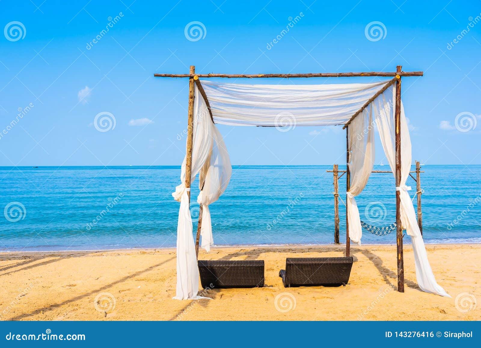 Przewodniczy parasol i hol na pi?knym pla?owym dennym oceanie na niebie