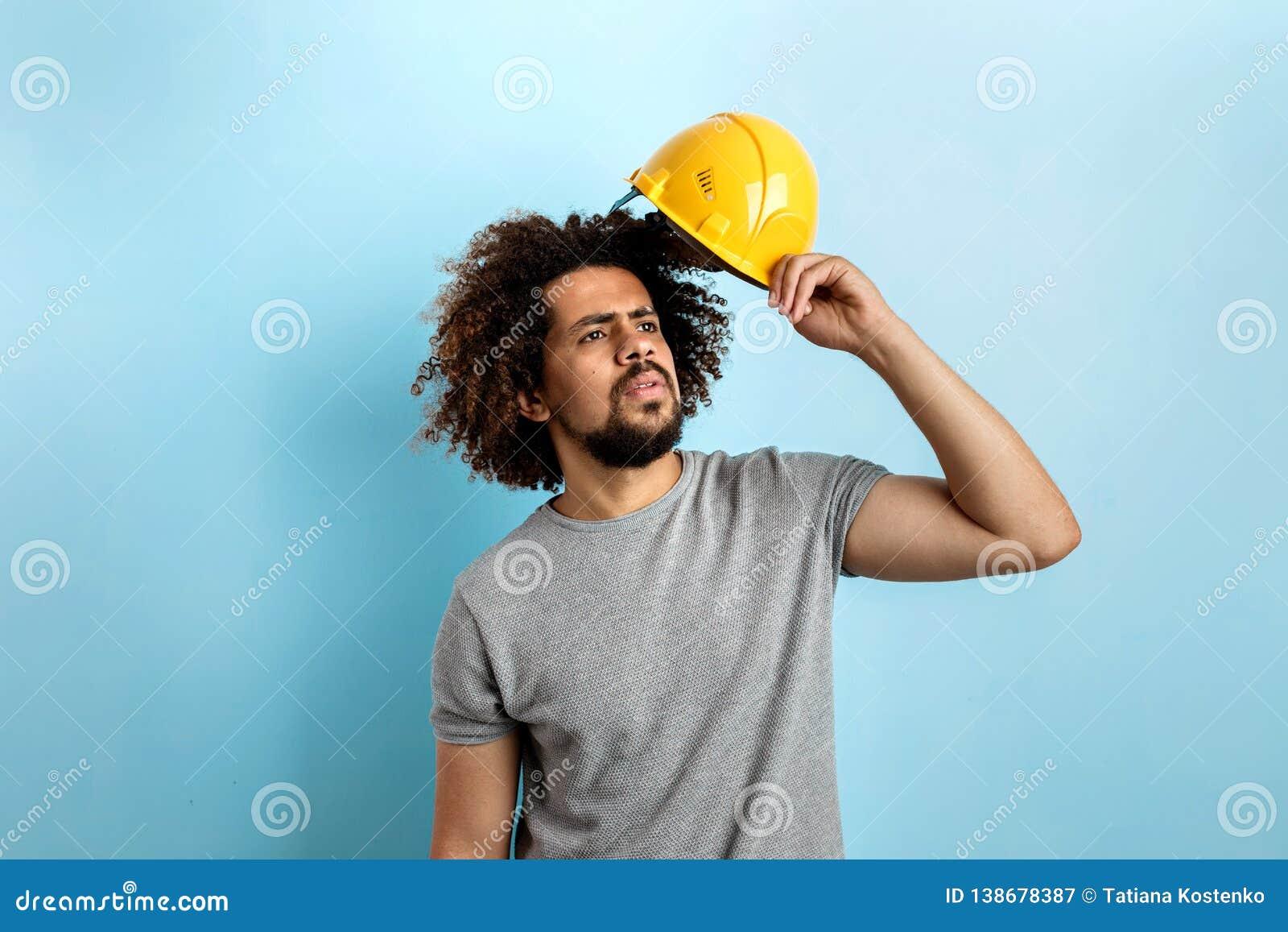 Przewodzący przystojny mężczyzna jest ubranym szarą koszulkę stoi z zbawczym hełmem patrzeje z ukosa z skoncentrowanym