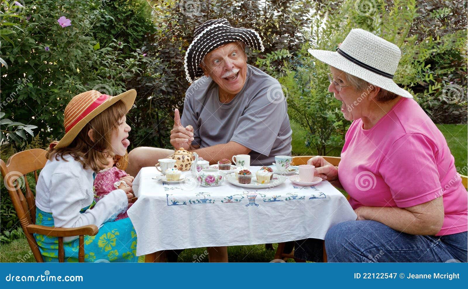 Przy ogrodowym herbacianym przyjęciem śmieszne twarze