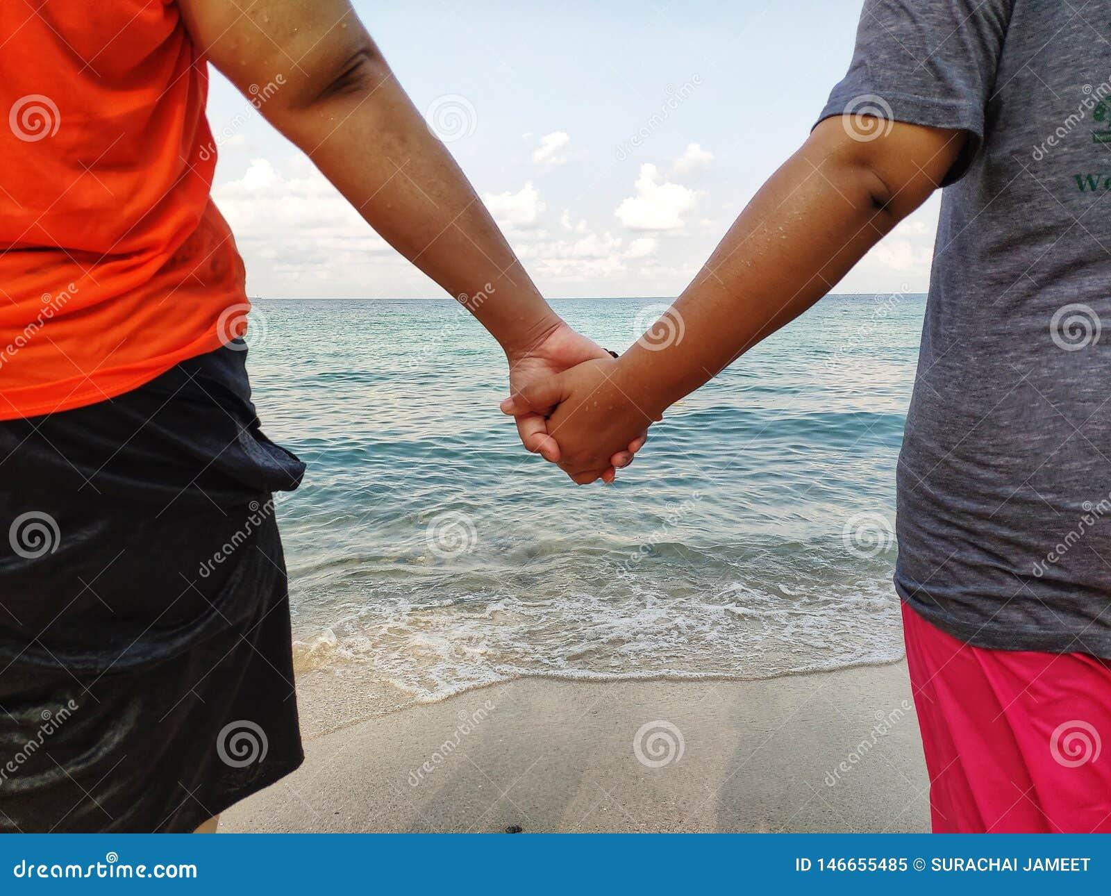 Przy plażą tam są kochankowie trzyma ręki chodzić puszek morze poj?cia t?a ramy piasek seashells lato
