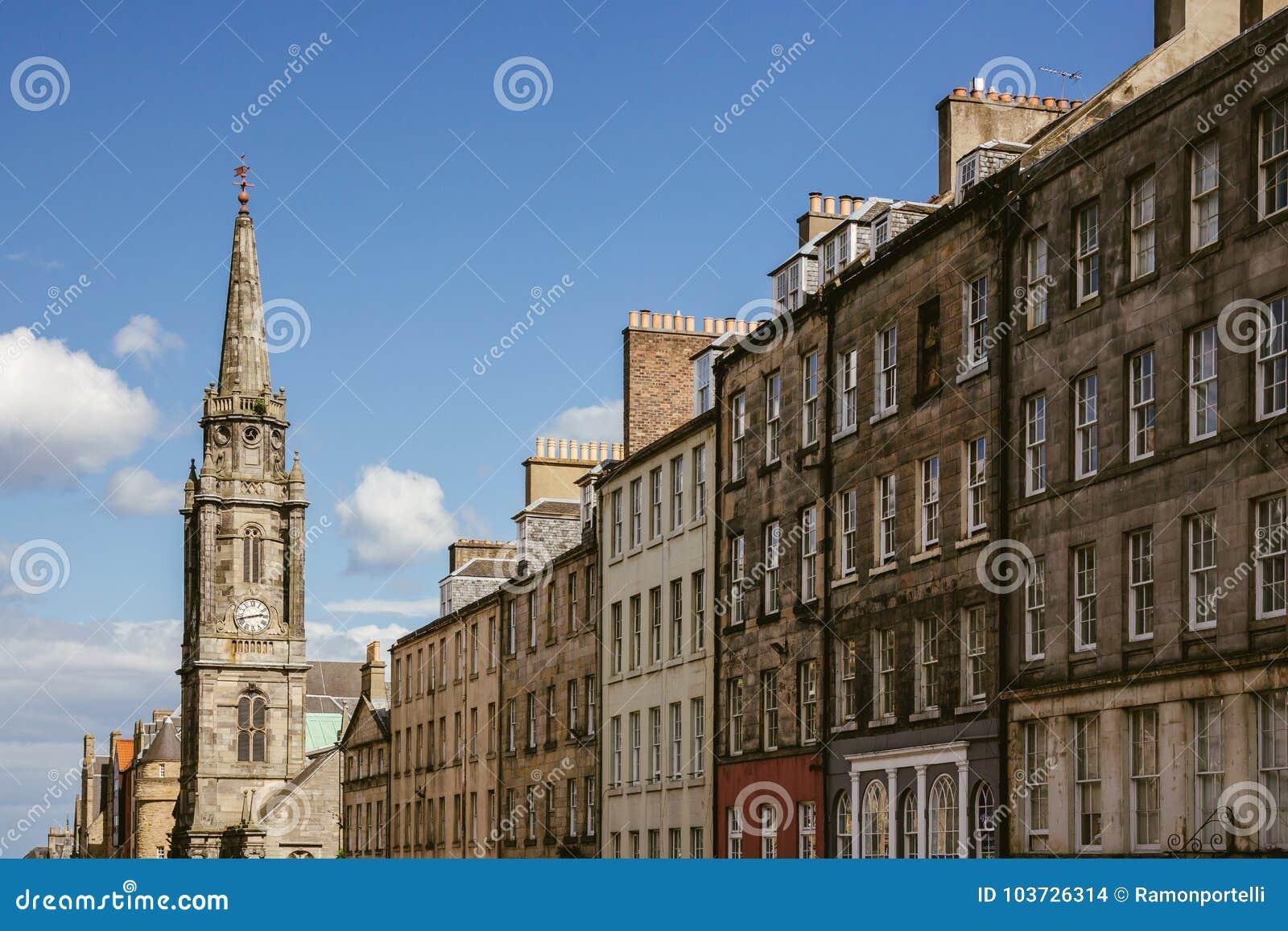 Przyglądający przy rzędem domy i kościelny steeple w Edynburg up