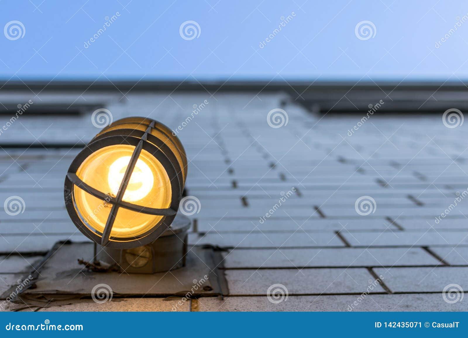 Przyglądający w górę wysokiej zewnętrznej ściany z zamazanym za oprawie oświetleniowej w przedpolu,