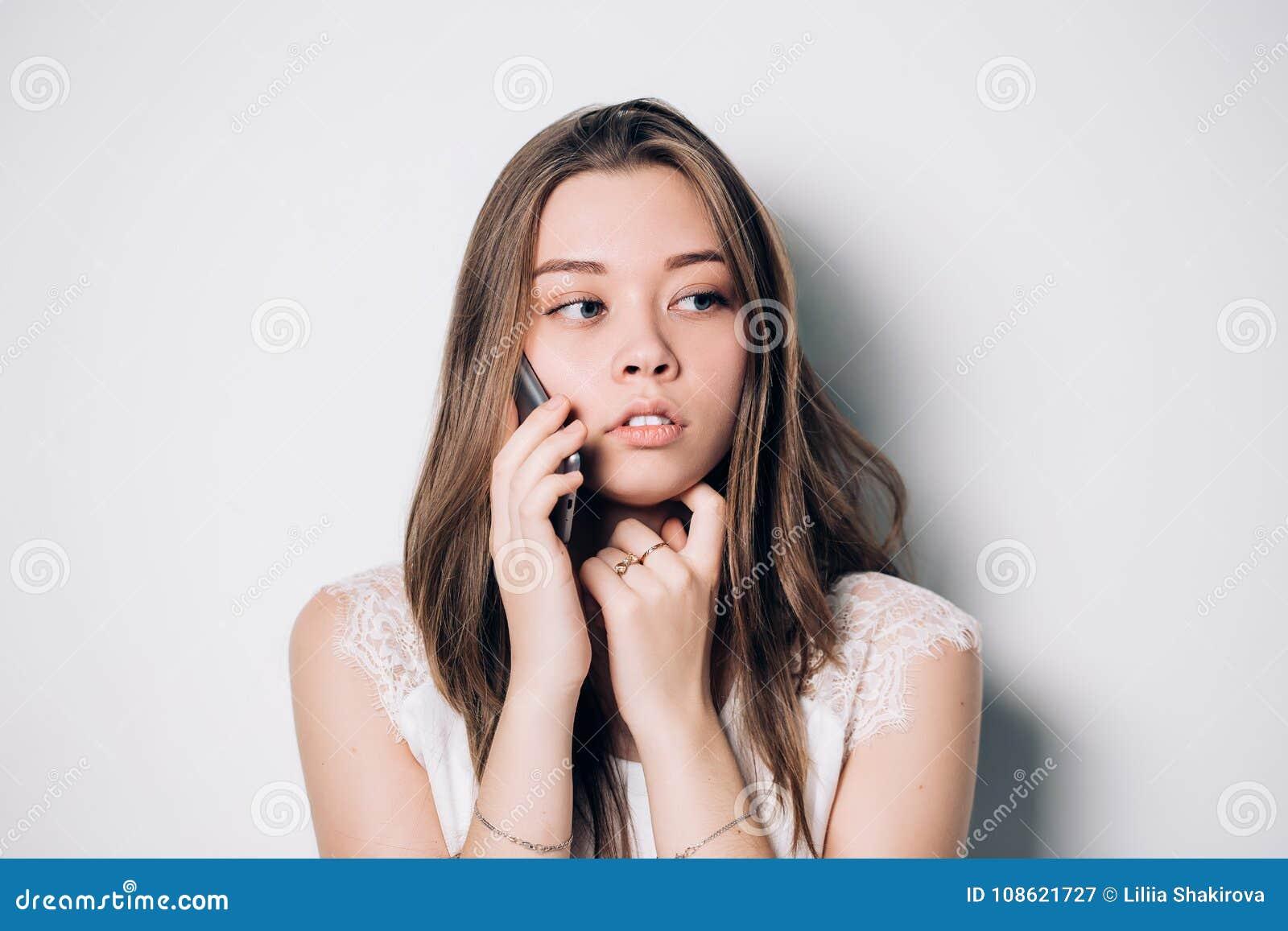 Przygnębiona, nieszczęśliwa młoda kobieta używa jej mądrze telefon,