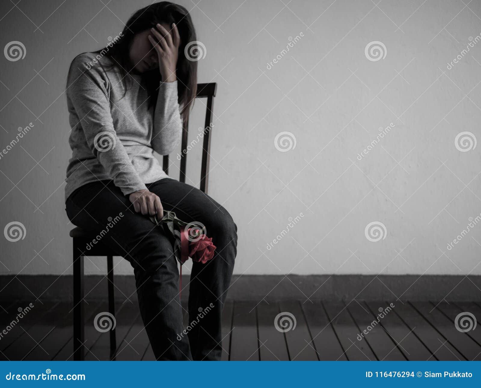 Przygnębiony łamający hearted kobiety obsiadanie, płacz z czerwieni różą i