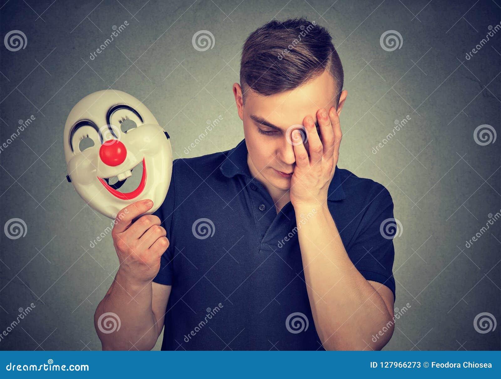 Przygnębiony mężczyzna z błazen maską