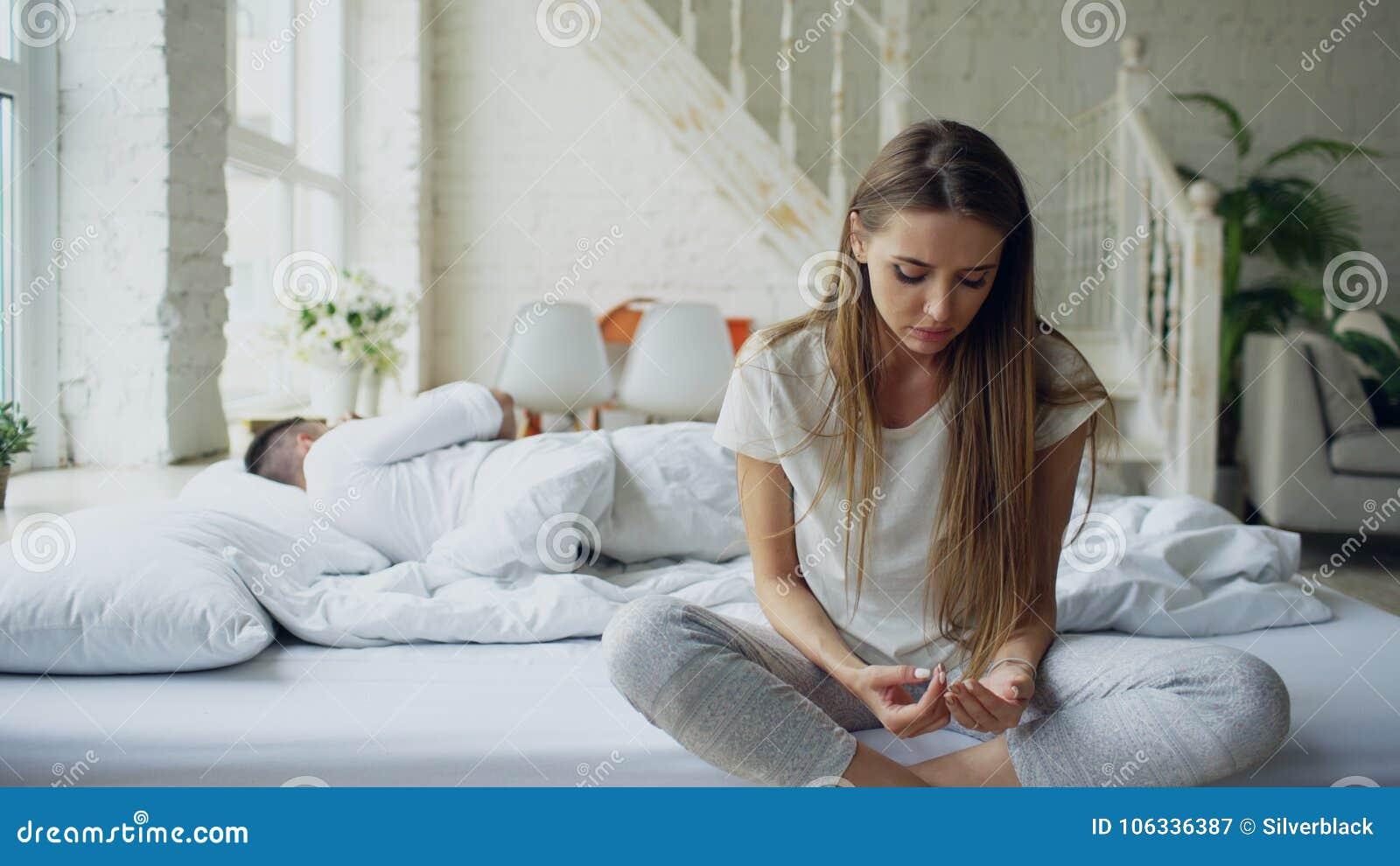 Przygnębiony młodej kobiety obsiadanie w łóżku i płaczu podczas gdy jej boylfriend lying on the beach w łóżku w domu
