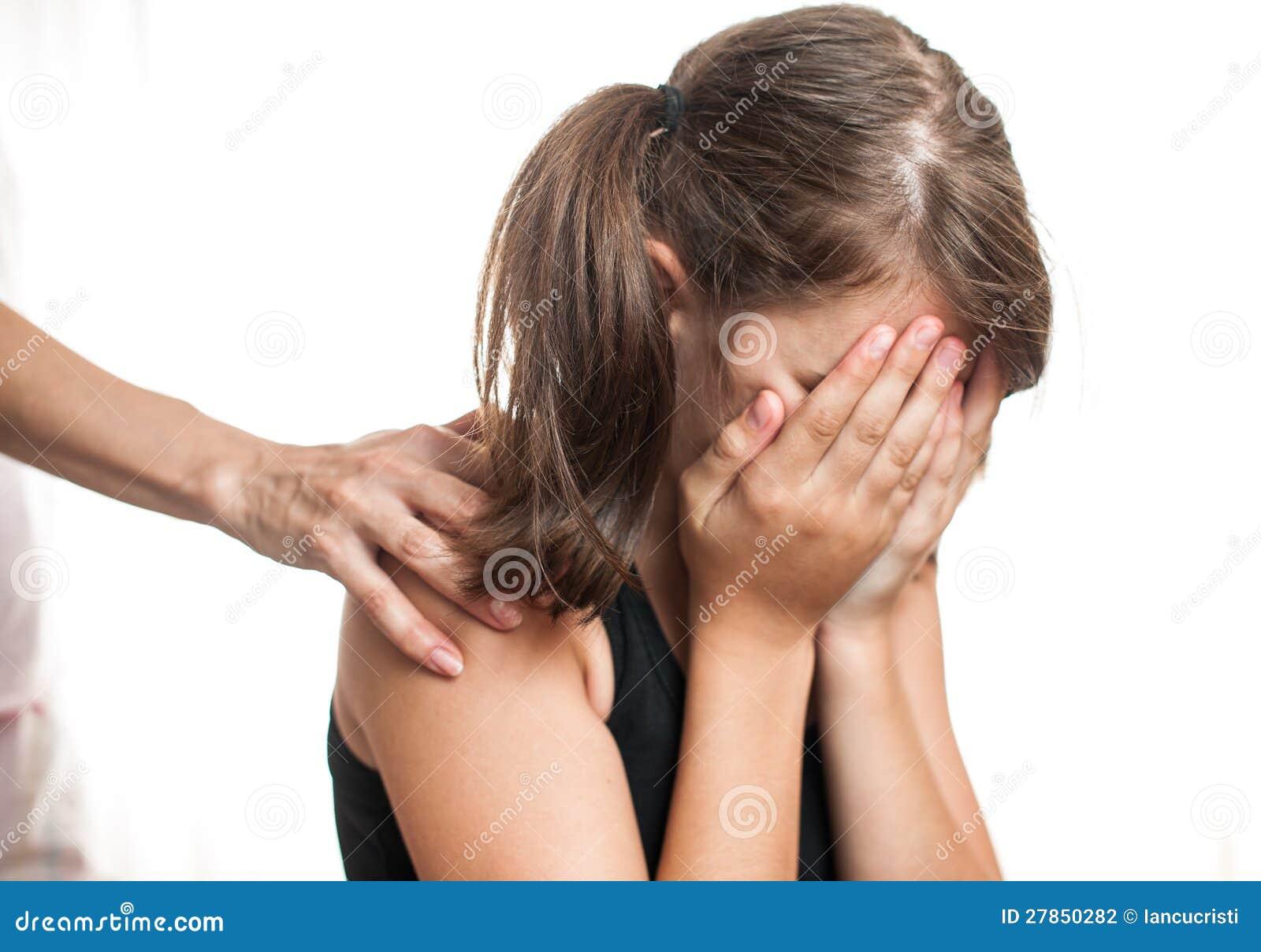 Przygnębiony nastolatka obsiadanie podczas gdy ręki przybycie od behind
