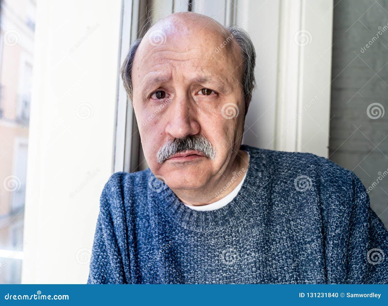 Przygnębiony stary człowiek patrzeje przez nadokiennego czuciowego samotnego i nieszczęśliwego cierpienia od depresji