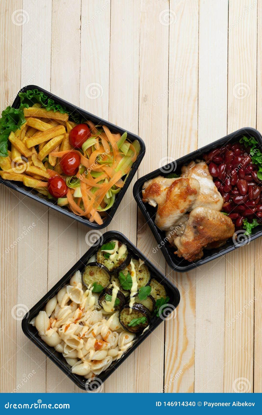 Przygotowywa posi?ek je?? na drewnianym stole, czerwone fasole, piec kurczak?w skrzyd?a, ober?yny, zucchini
