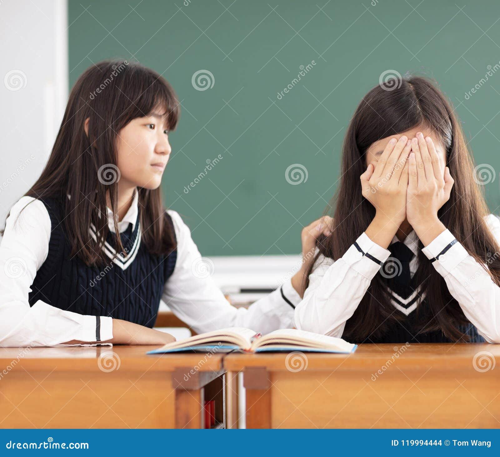 Przyjaciel pociesza smutny uczeń w sala lekcyjnej