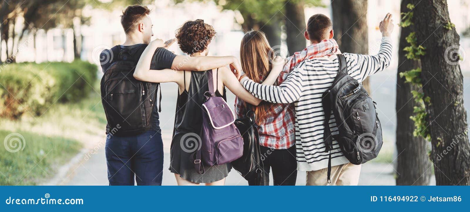 Przyjaciele ściska chodzić w mieście z plecakami