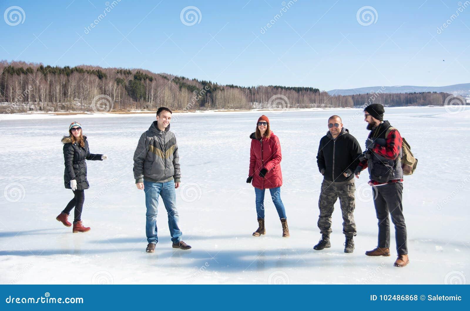 Przyjaciele ma zabawę na zamarzniętym jeziorze