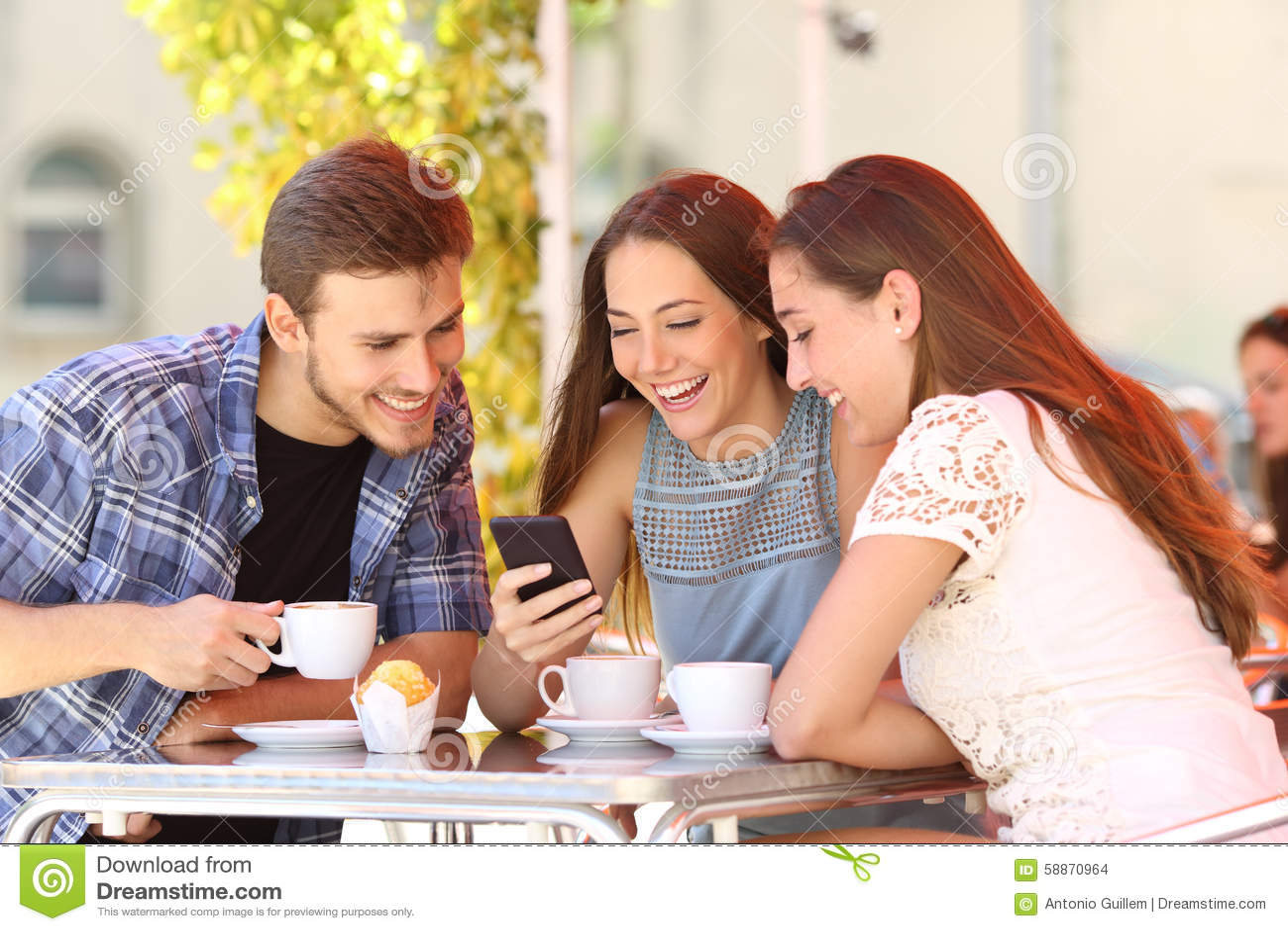 Przyjaciele ogląda środki w mądrze telefonie w sklep z kawą