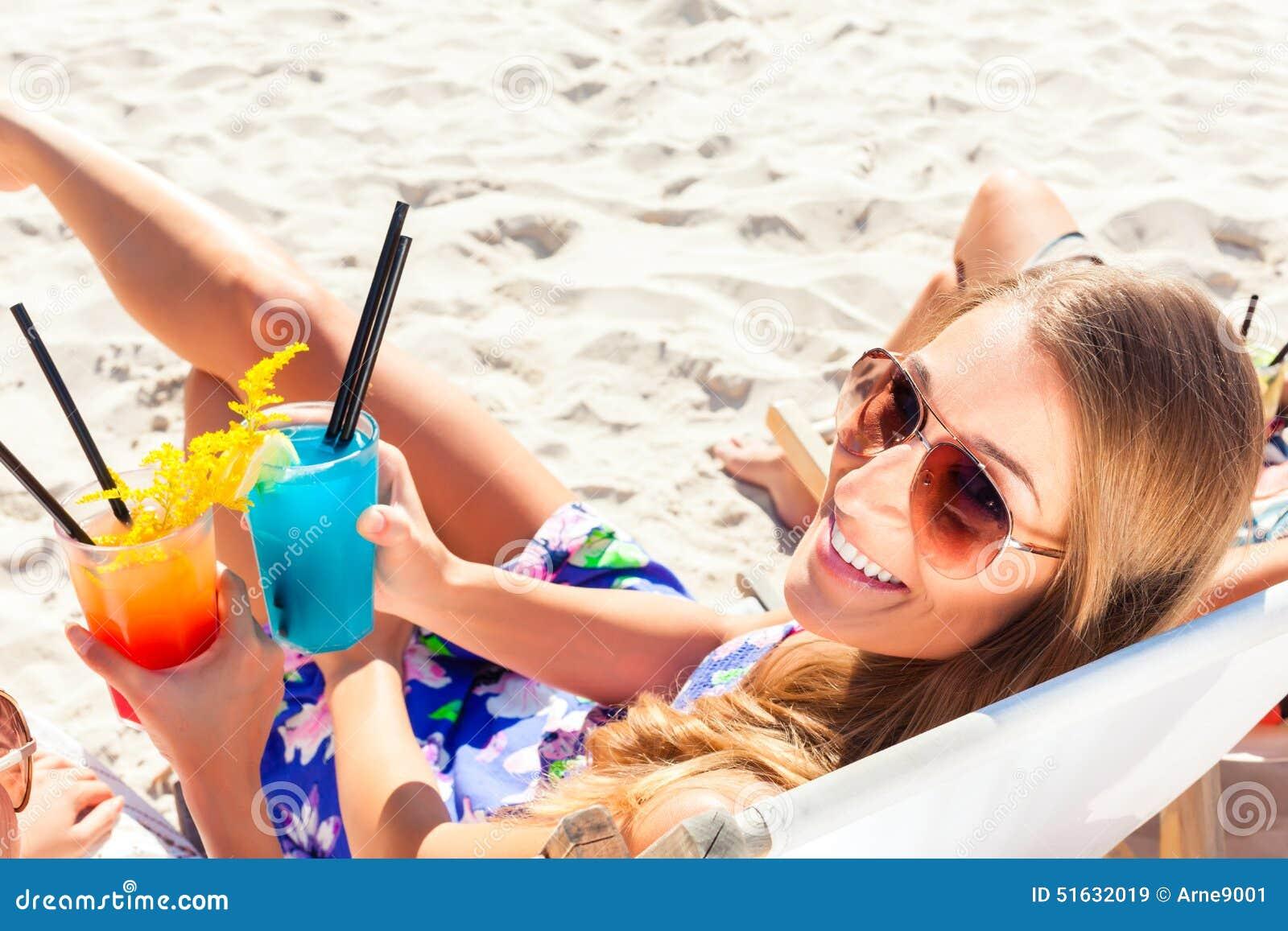 Przyjaciele pije koktajle w plaża barze