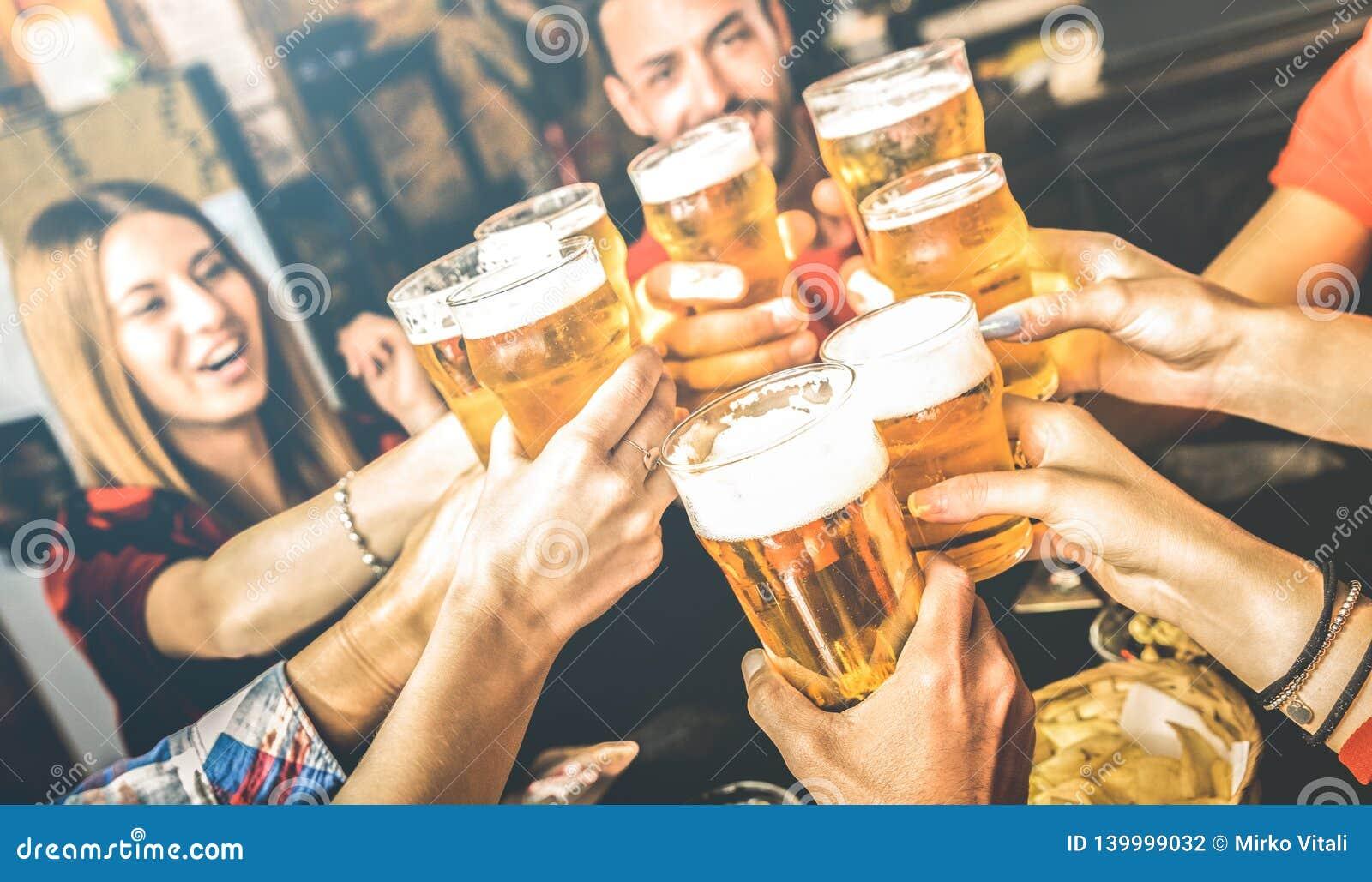 Przyjaciele pije piwo przy browaru baru restauracją na weekendzie - przyjaźni pojęcie z młodzi ludzie ma zabawę wpólnie
