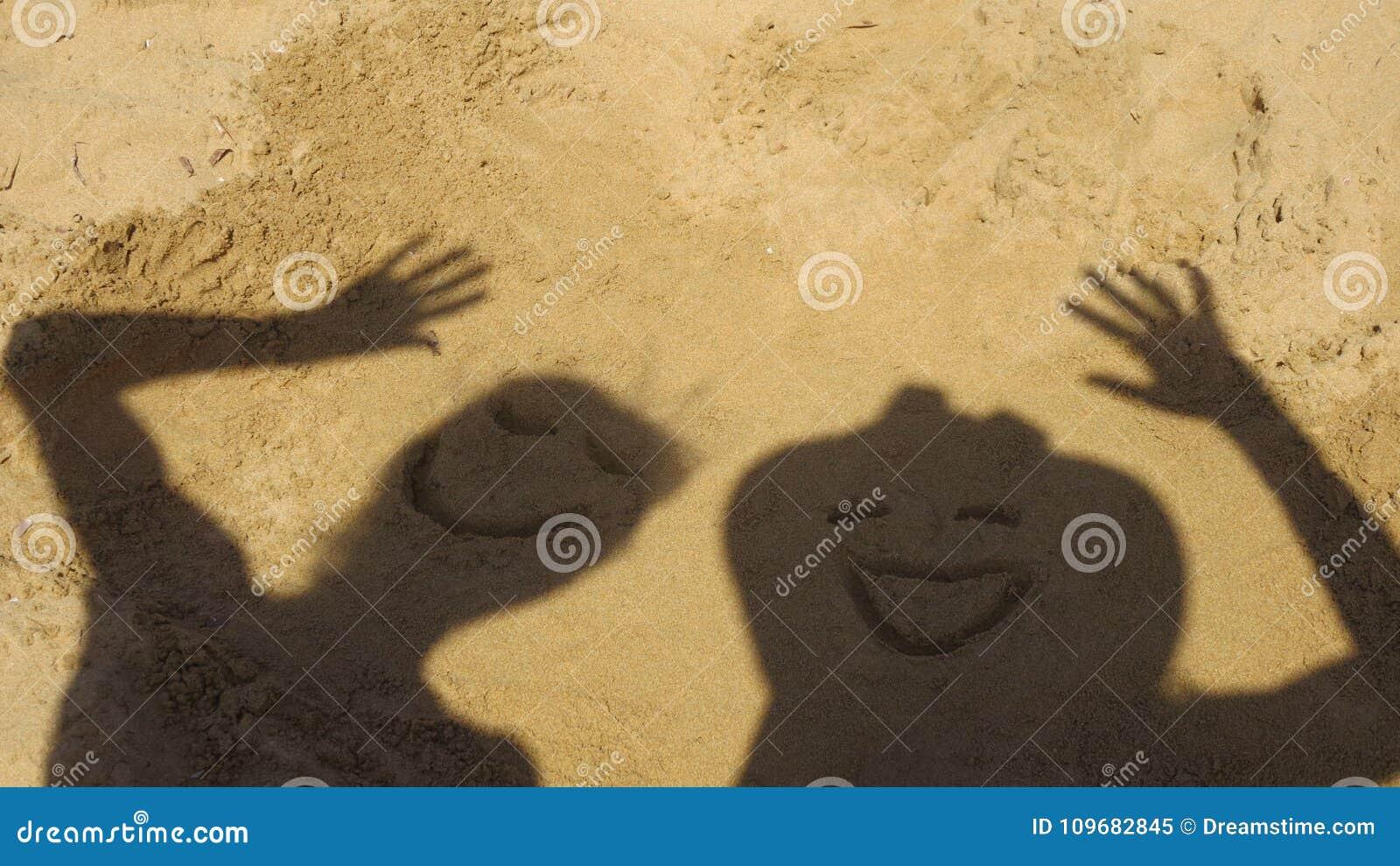 Przyjaciele robi śmiesznym twarzom w piasku