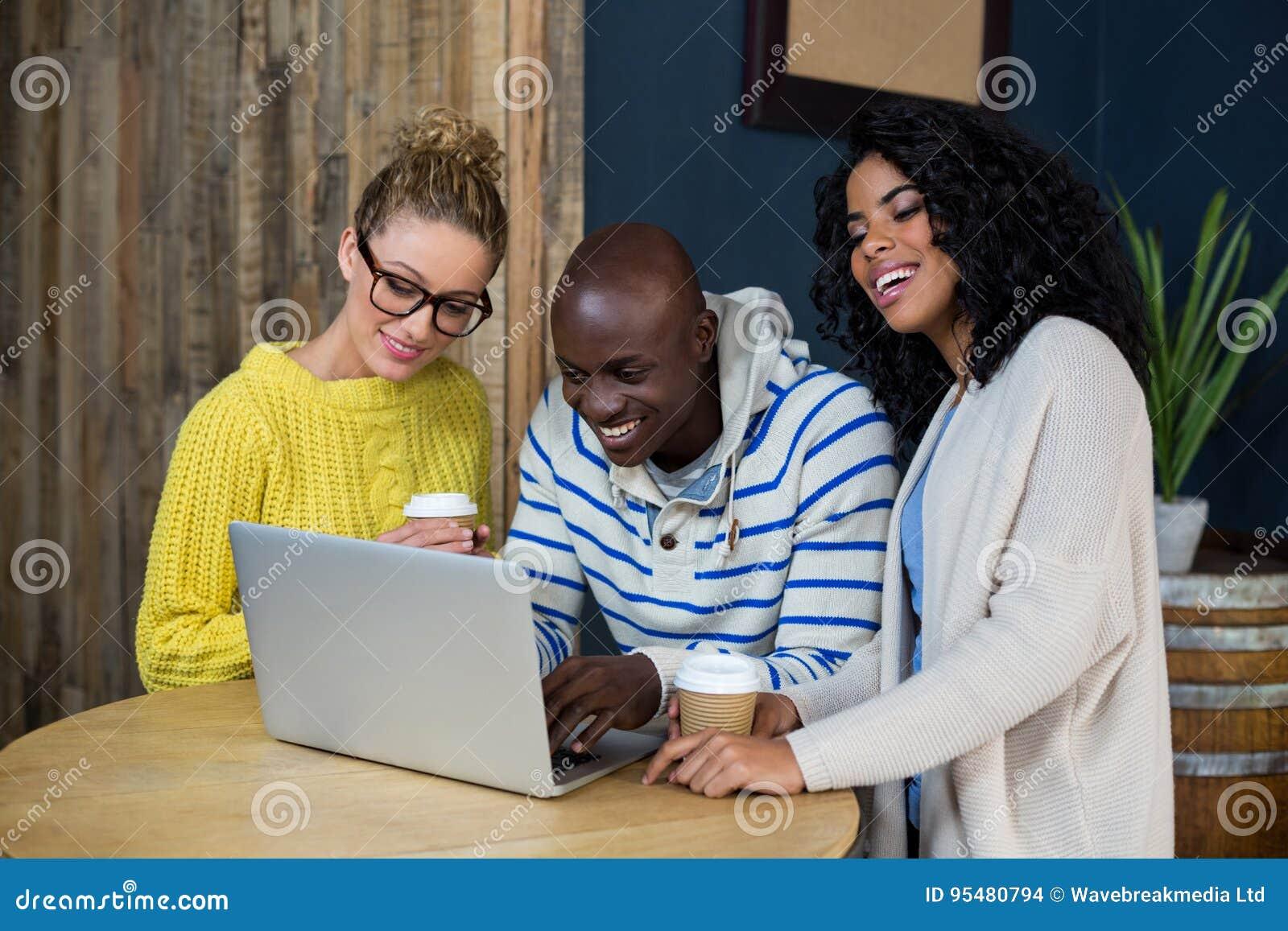 Przyjaciele używa laptop podczas gdy mieć kawę w café